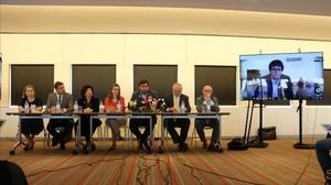 Toni Comín,Meritxell Serret yLluis Puig junto con los abogados belgas y Carles Puigdemont en pantalla, durante la rueda de prensa de presentación de la demanda en Bruselas, el pasado 5 de junio.