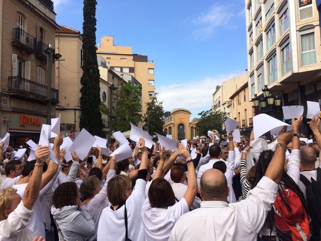 Los concentrados en la manifestación a favor del diálogo en Terrassa alzan sus brazos con papeles en blanco.