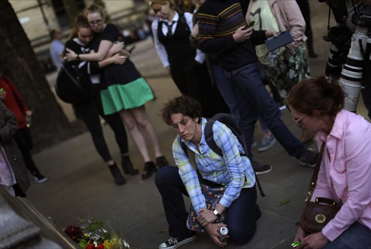 lpedragosa38574952 people stand next to flowers after a vigil in albert square 170523222036