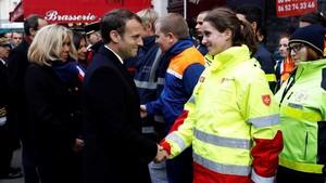 Macron y su mujer, Brigitte (izq), saludan a miembros de los servicios de emergencia delante del bar Comptoir Voltaire, durante una ceremonia por el segundo aniversario de los atentados de París, el 13 de noviembre.