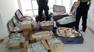 Maletas y cajas con enormes fajos de billetes de la divisa brasileña, en el piso registrado por la policía, en Salvador de Bahía, el 5 de septiembre.