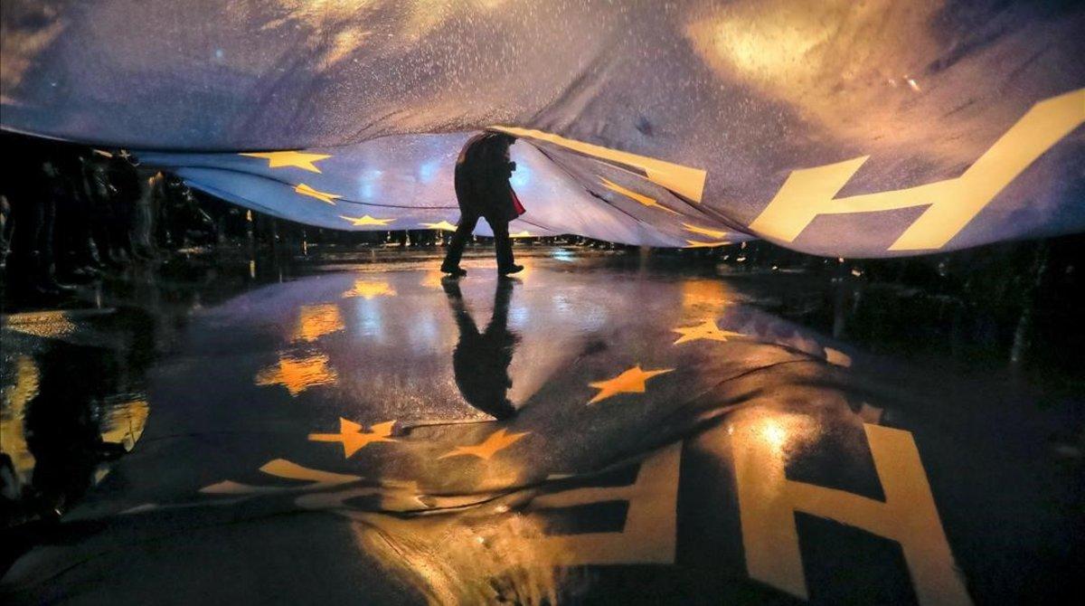 Un manifestante camina bajo una gran bandera de la Unión Europea durante una protesta frente al Parlamento rumanocontra las políticas del Gobierno del país.