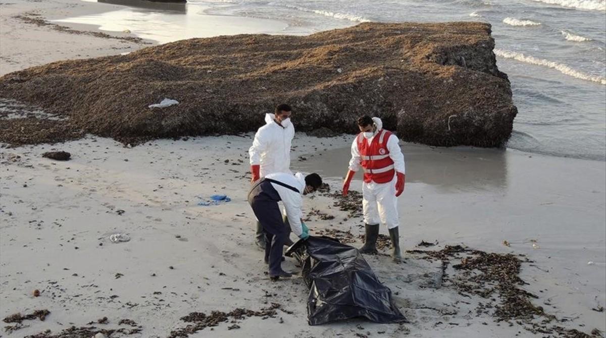 Miembros de la Media Luna Roja libia retiran el cadáver de un inmigrante fallecido en su intento de llegar a territorio europeo.