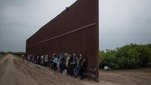 Migrantes centroamericanos aguardan en el lado mexicano del muro a cruzar al lado estadounidense.