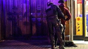 Un mosso registra a un joven en las inmediaciones de la plaza Urquinaona, durante los dispositivos preventivos situados en Barcelona este martes.