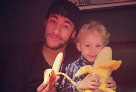 Neymar es menja un plàtan al costat del seu fill, que sosté un plàtan de peluix.