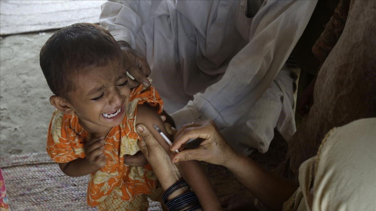 Una doctora pone una vacuna a un niño en un campo de refugiados en Pakistán.