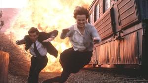 Pierce Brosnan yFamke Janssen, en una explosiva escena de la película Goldeneye.