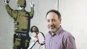 Cañete este martes frente alareproduccion de un mural del artista Banksy sobre el muro de Belénque se exhibe en la exposicion 'The World of Banksy',en el Espacio Trafalgar de Barcelona.