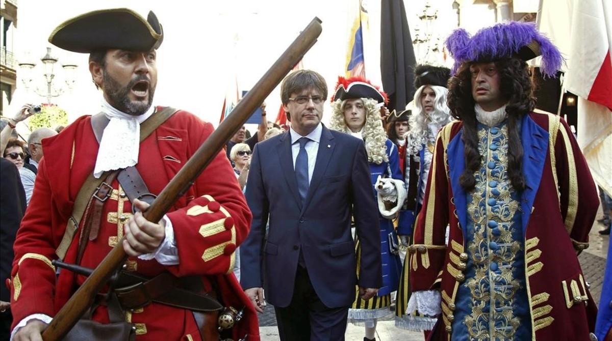 El 'president' Carles Puigdemont recibe a una representación de los Miquelets de Catalunya y de la Associació de Recreació Històrica La Coronela en el Palau de la Generalitat.