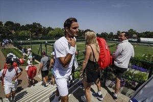 Roger Federer camina entre los aficionados tras entrenarse en las pistas de Wimbledon