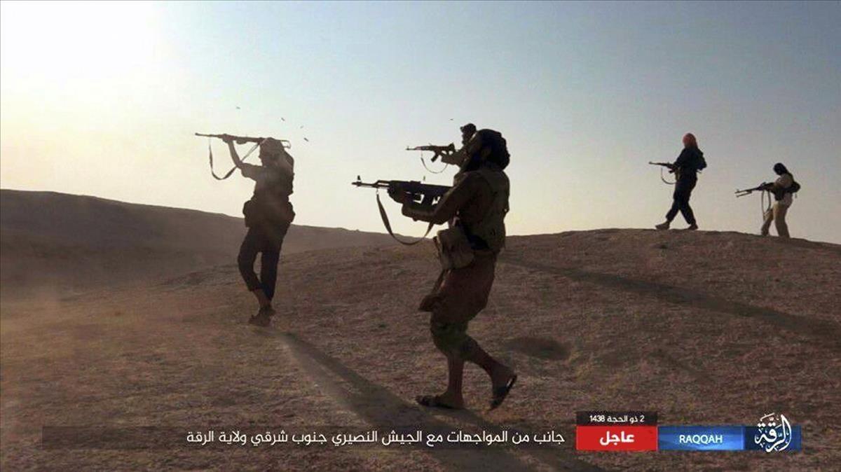 Supuestos combatientes del EI disparan sus armas en enfrentamientos con tropas del régimen sirio en el sudeste de Raqqa, en una imagen difundida el 24 de agosto.