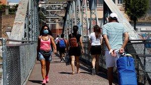 Vecinos cruzan el puente de la Torrassa en L' Hospitalet de Llobregat,barrio donde hay un nuevo brote de la COVID-19.