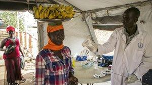 Un trabajador sanitario comprueba el estado de varias personas en la frontera de Nimule, en Uganda.
