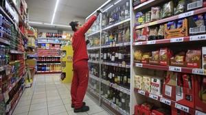Una empleada repone los productos en un supermercado.