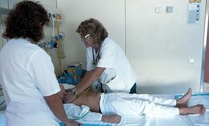 Una médica y una enfermera atienden a un paciente en el Vall dHebron.