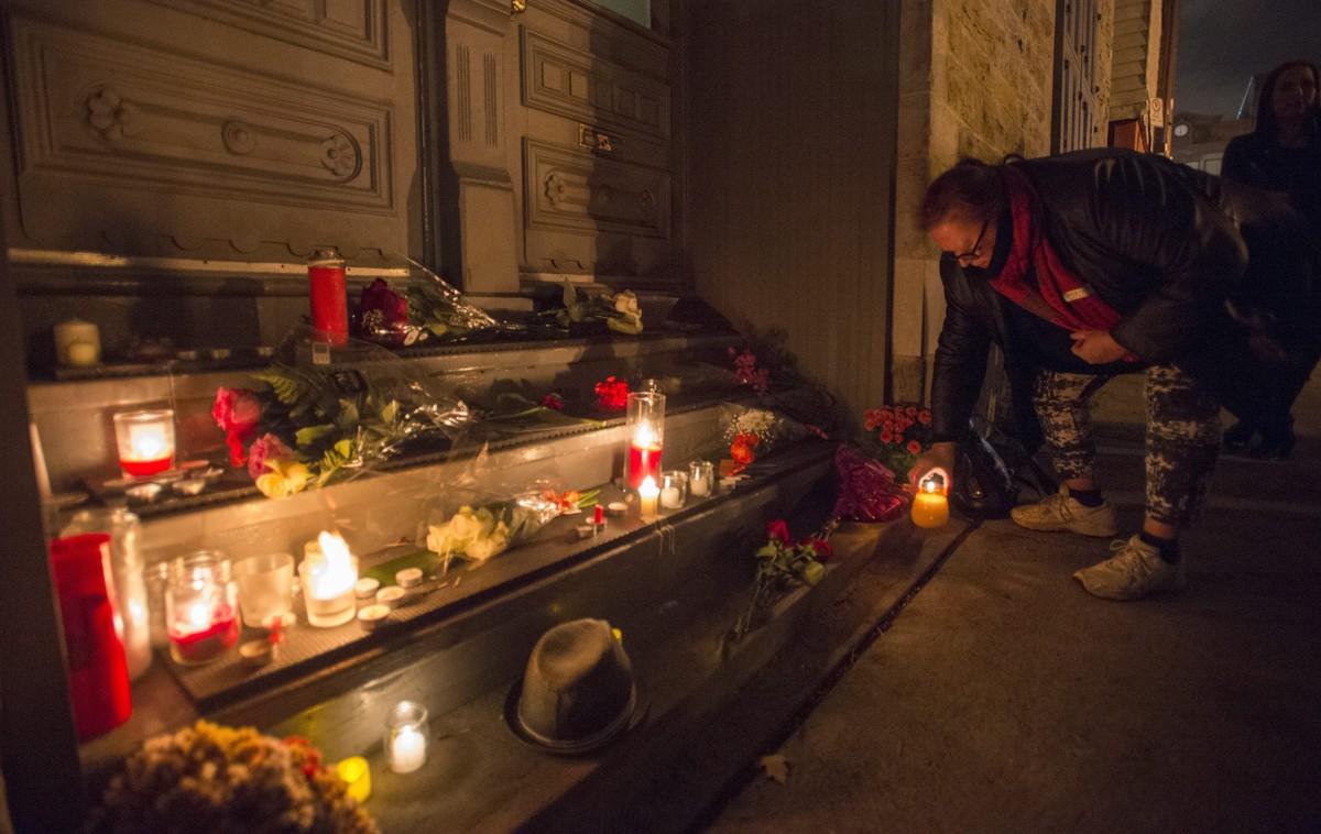 Una mujer enciende una vela frente a la vivienda de Leonard Cohen en Montreal, este jueves.