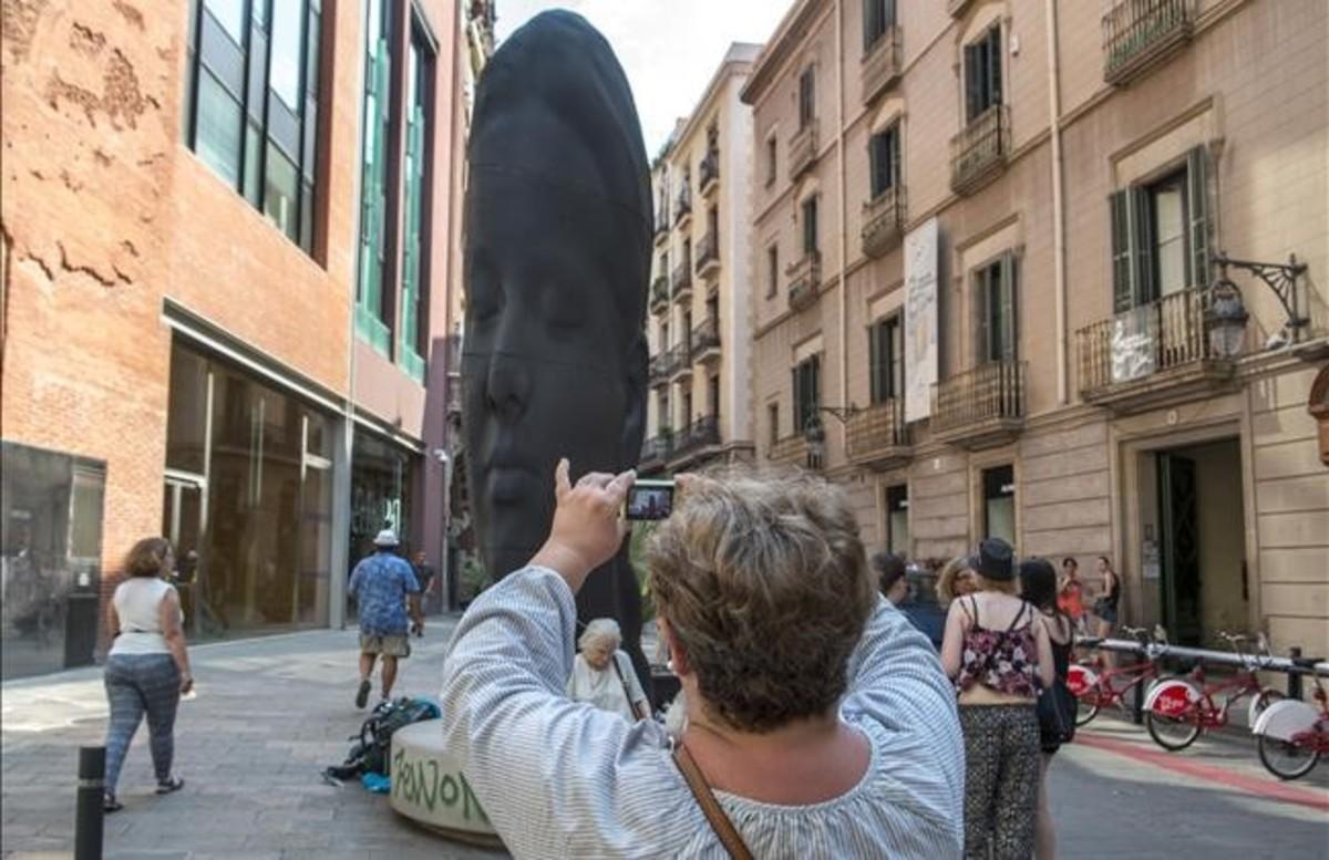 Una turista fotografía a 'Carmela', la escultura de Jaume Plensa que maravilla a los visitantes ante el Palau de la Música.