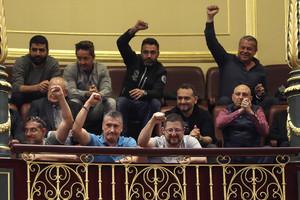 Un grupo de estibadores saludan desde la tribuna de invitados del Congreso donde hoy se debatia el real decreto ley de reforma de la estiba.