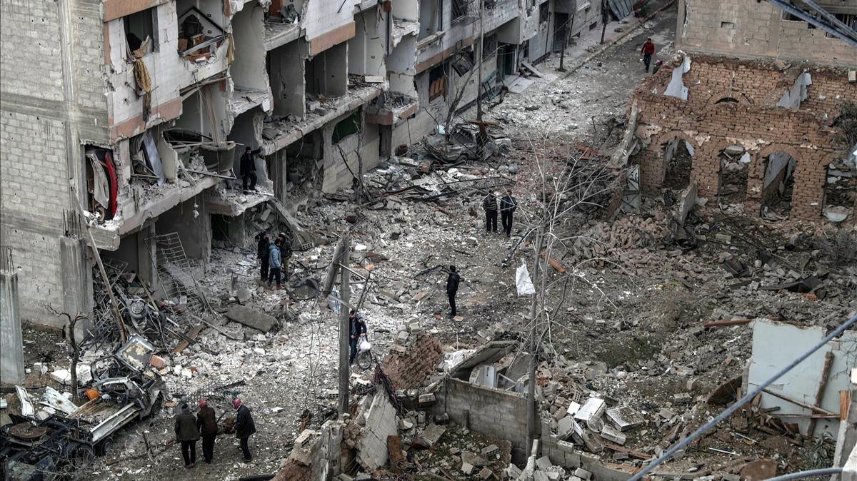 Vecinos inspeccionan los edificios en ruinas tras varios bombardeos el día anterior en Duma, feudo rebelde de Guta Oriental (Siria), el 22 de febrero.