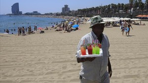 Vendedores ambulantes de mojitos preparan la bebidaparavenderlaen la playa de la Barceloneta