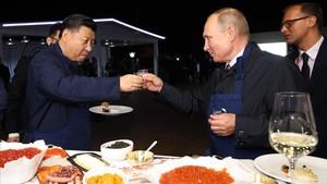 El presidente ruso,Vladimir Putin, brinda con suhomólogo chino,Xi Jinping, en una feria alementaria en Vladivostok.