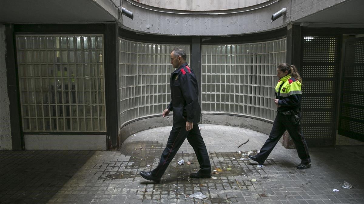Dos mossos patrullan por lo sbajos de un edificio de La Mina.