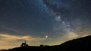 Un meteorito cruza el cielo mientras se puede observar Marte (centro) y la Vía Lactea (derecha) durante una lluvia de perseidas.