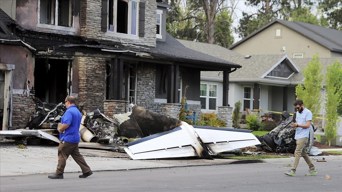 Investigadores oficiales revisan el lugar del impacto de la avioneta.