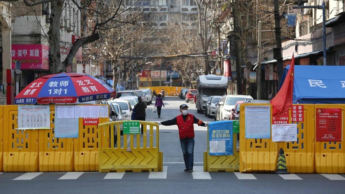 Un voluntario cierra el acceso a un barrio de Wuhan, en China, el pasado 15 de marzo.