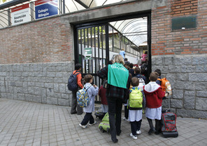 Padres y niños, a la entrada de un colegio de Madrid, este jueves.