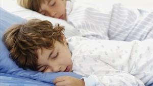Dos niños en edad escolar durmiendo.