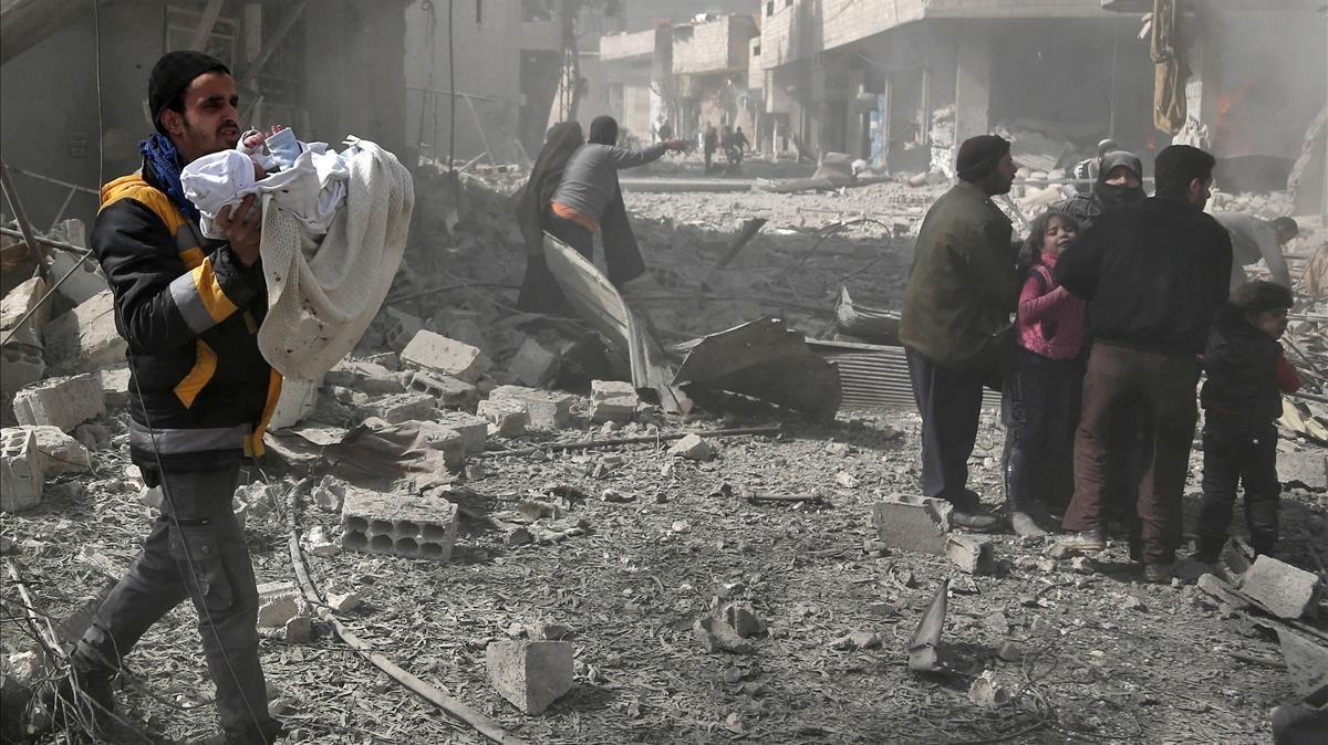 Un hombre lleva en brazos a un bebé rescatado entre las ruinas de un edificio tras el bombardeo de Guta por parte de las fuerzas del régimen de Damasco.