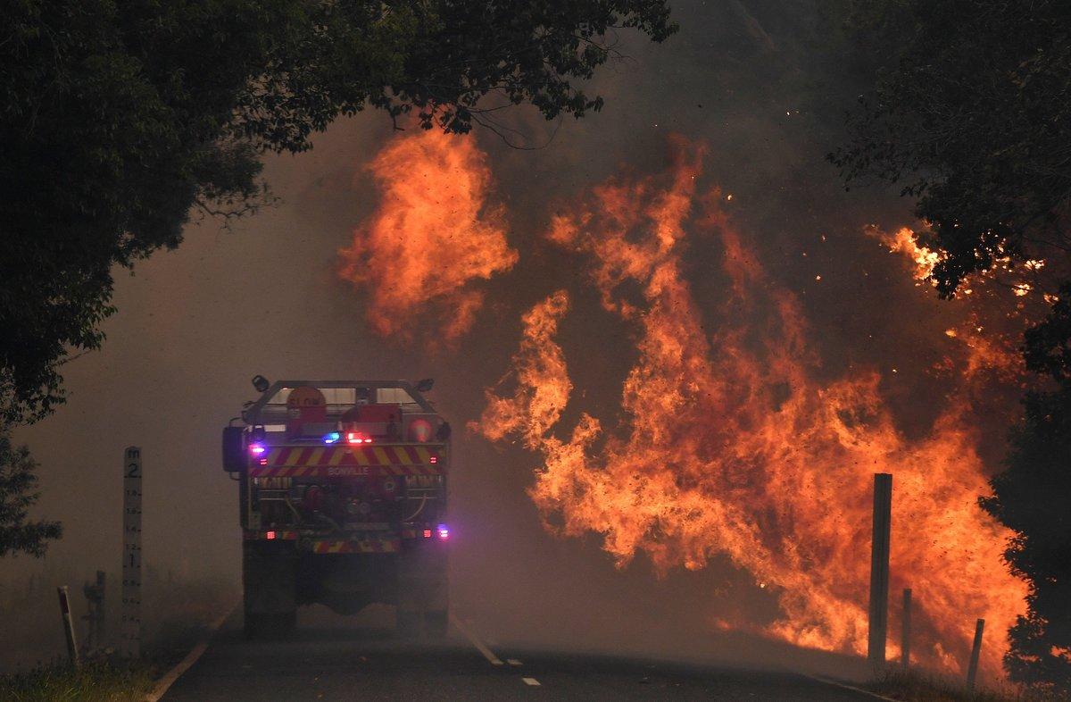 12 November 2019, Australia, Coffs Harbour: A fire truck passes by a bushfire near Nana Glen. Photo: Dan Peled/AAP/dpa