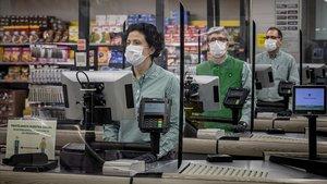 Cajeros de Mercadona con mascarillas y tras unas mamparas de protección, el 24 de marzo pasado, en València.