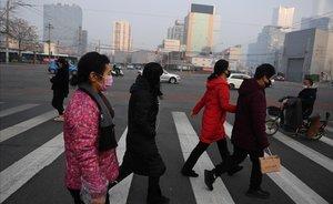 Calle concurrida en Beijing, con ciudadanos protegidos con máscaras por miedo al contagio por coronavirus.