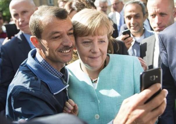 La cancillera se hace un selfi con un refugiado durantesuvisita ala oficina dede Migración de Berlín.