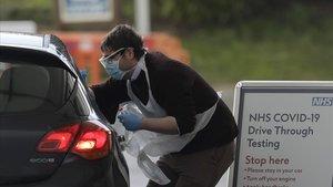 Un conductor se somete al test para saber si está afectado por Covid-19 en el parque temático Chessington, en Londres.
