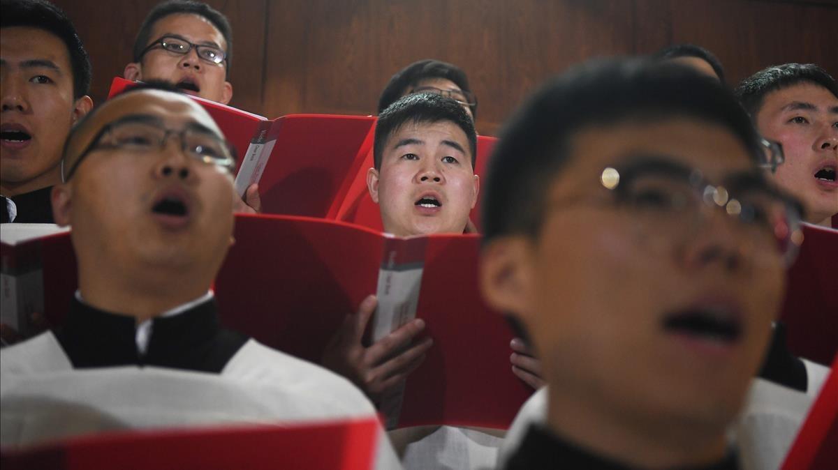 Un coro canta durante la misa de Jueves Santo, en Pekin.