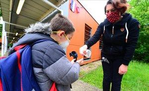 Una maestra aplica gel hidroalcohólico en las manos de un alumno que llega a la escuela Jean-Jaures, en la localidad francesa de Cenon.