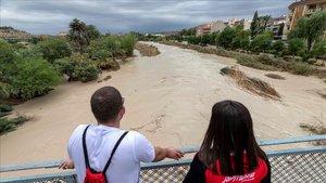 Dos chicos observan la crecida del río Segura tras desbordarse por las dos márgenes a su paso por Archena, Murcia.