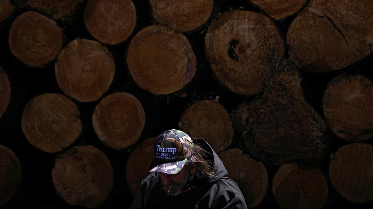 Un hombre se enciende un cigarrillo junto a un almacén de troncos de madera en un mitin de Donald Trump en el aeropuerto de Traverse City, enMichigan.