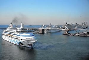 Un ferri fumejant entra per la Bocana Nord prop del moll Adossat, ple de grans creuers.