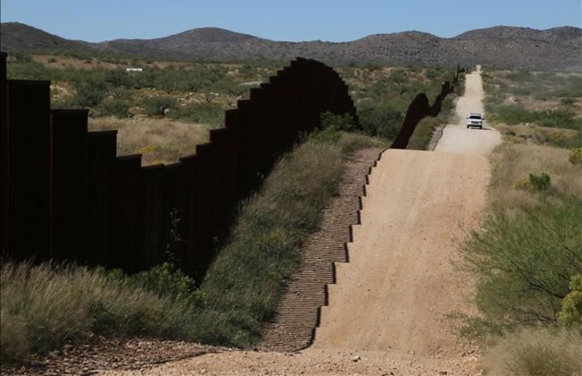 Un coche de la Patrulla Fronteriza vigila la valla que separa México de EE UU asu paso por Sasabe, en el desierto de Sonora.