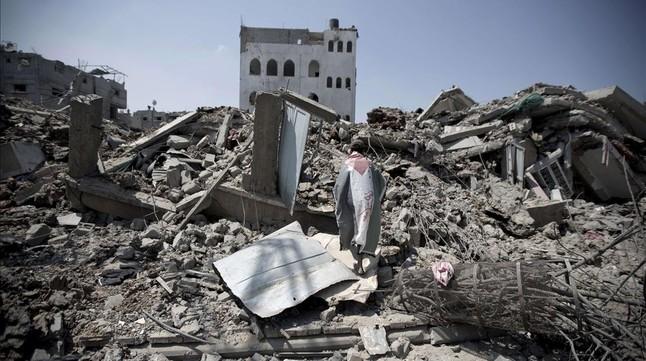 Un hombre con la bandera palestina camina por los escombros de edificios destruidos en el barrio de Shayahía, en la ciudad de Gaza, este lunes.