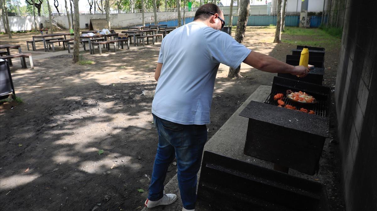 Un hombre asa carne en una de las barbacoas del parque de Trinitat Vella, este martes.