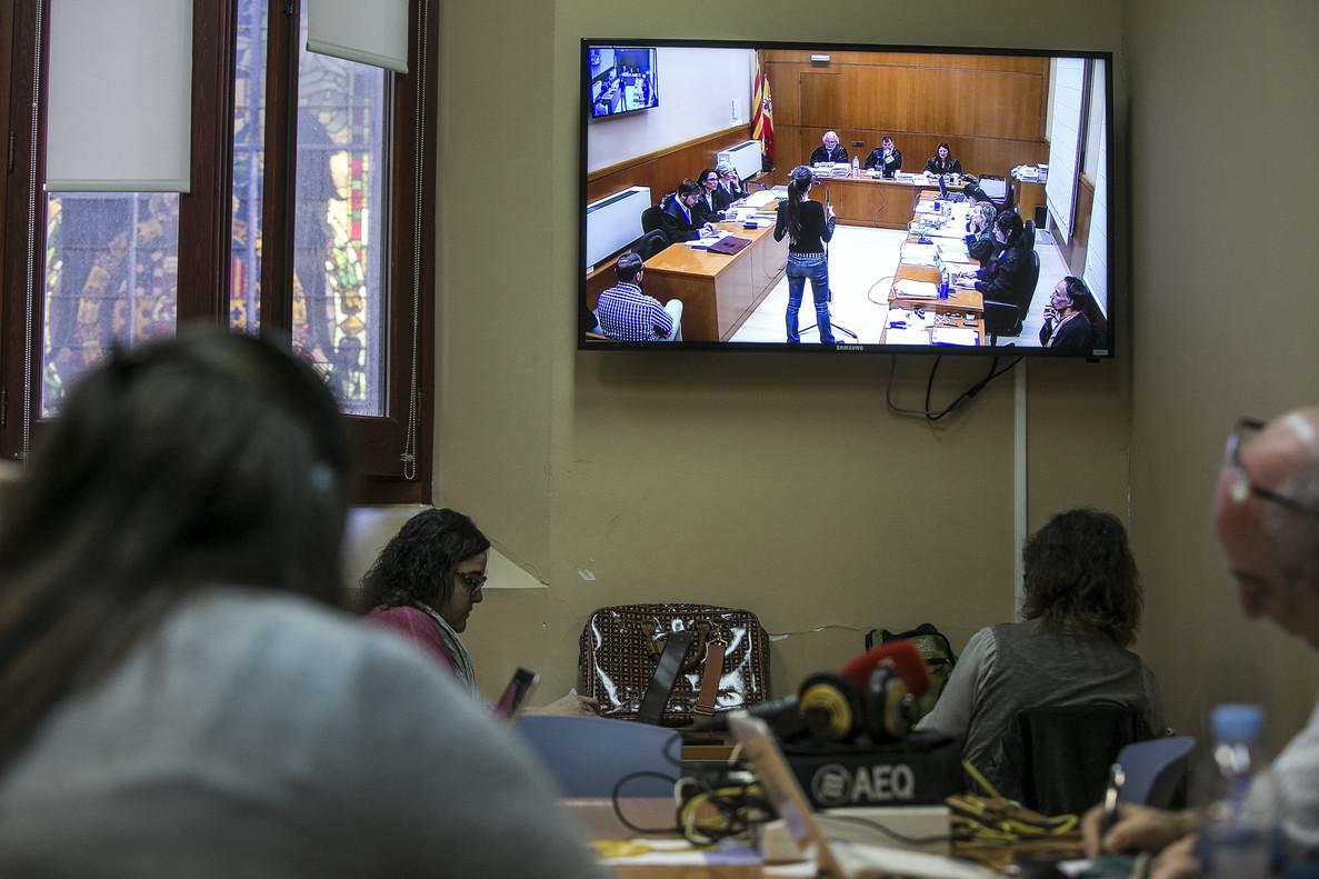 Periodistas siguen la declaración de una testigo por un monitor, en la Audiencia de Barcelona.