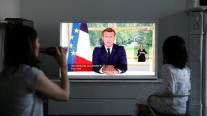 Una familia sigue este domingo el mensaje a la nación del presidente francés, Emmanuel Macron.