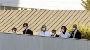 El presidente francés, Emmanuel Macron, a la izquierda de la foto con mascarilla, y el profesorDidier Raoult, en el centro de la imagen, con bata blanca y cabello largo rubio,ayer jueves en Marsella.