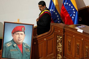 Venezuela s President Nicolas Maduro walks next to a painting of Venezuela s late President Hugo Chavez  during a special session of the National Constituent Assembly to present his annual state of the nation in Caracas  REUTERS Manaure Quintero File Photo